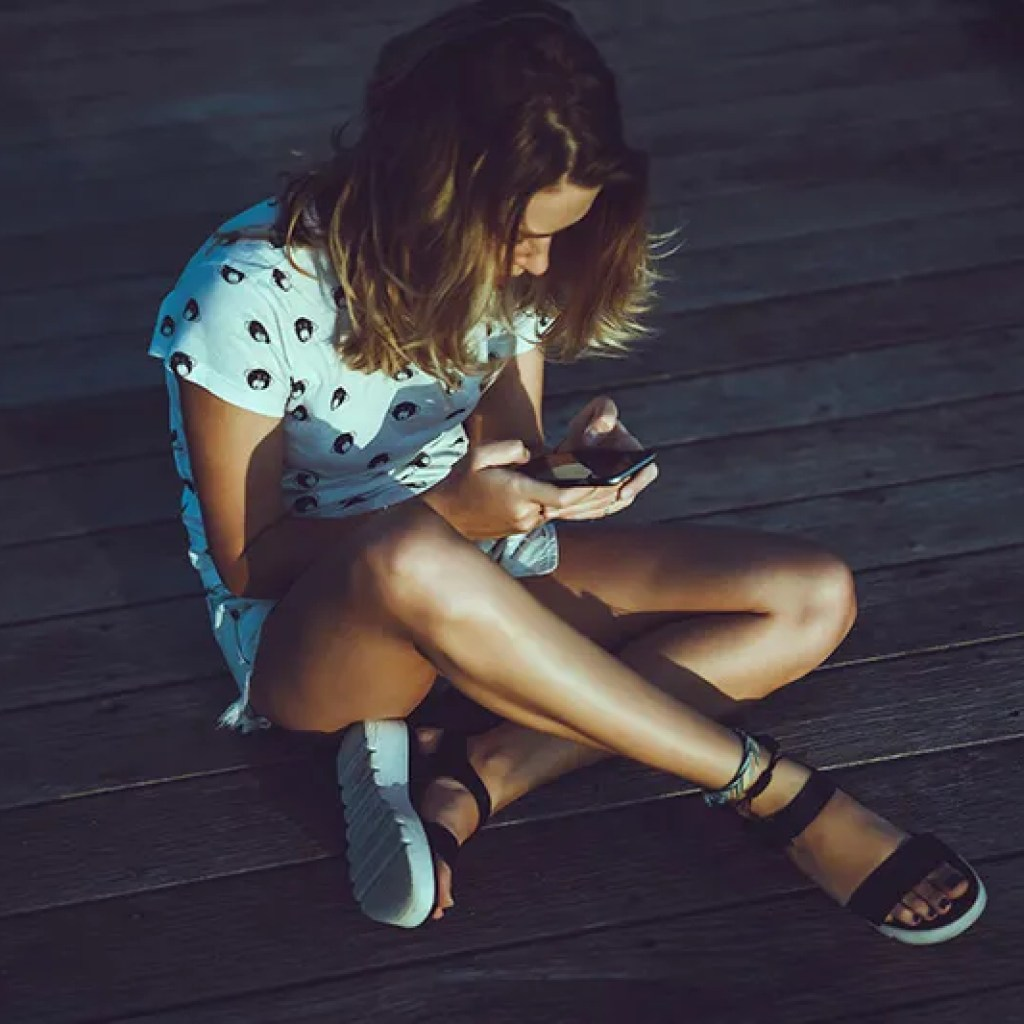 Chica sentada en el suelo interactuando con el movil