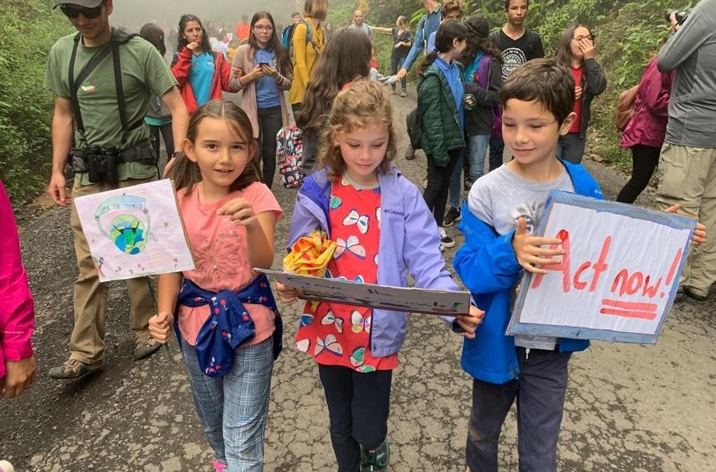 Niños y adultos marchan por el clima entre las nubes de Monteverde