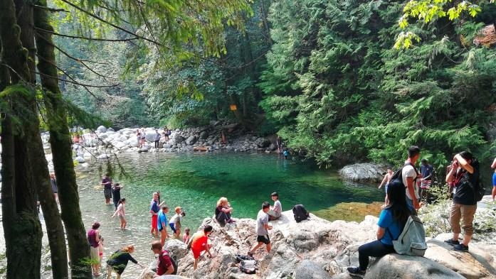 Lynn Canyon Park im Norden Vancouvers, türkisblaues Wasser mit Steinen darin und vom Bäumen umgeben