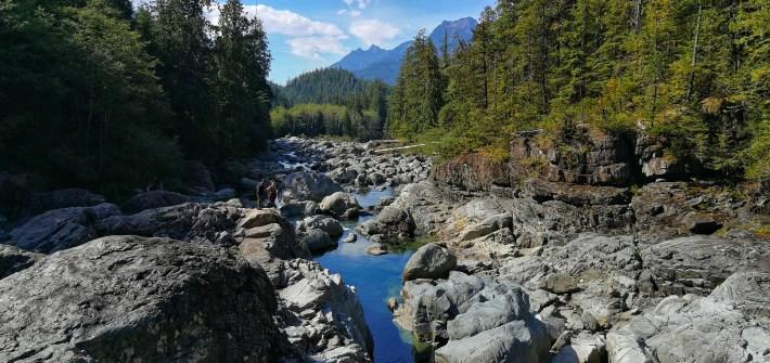 Schlucht mit Wasserfällen, Steinen und Bergen im Hintergrund