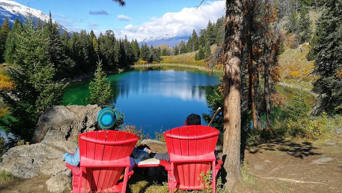 Zwei Personen sitzen auf roten Stühlen im Tal der fünf Seen