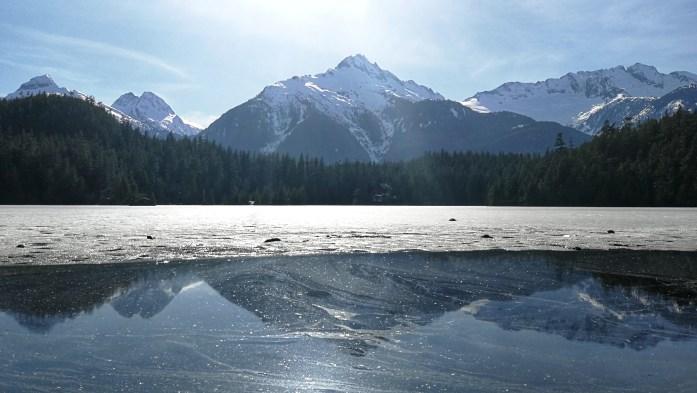 Aussicht auf einen noch zugefrorenen See umringt von Bergen