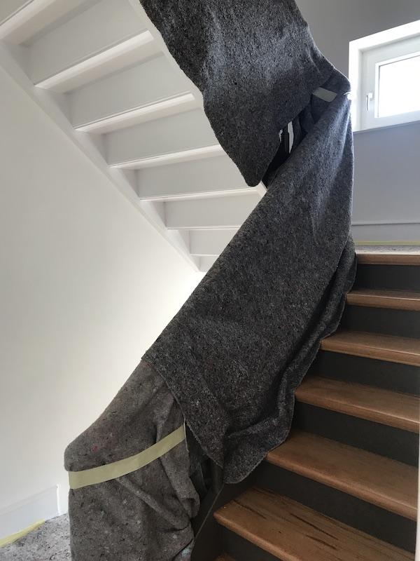 Bei einem Umzug mit unserem Bodenschutzservice decken wir auch Handläufe mit Möbeldecken ab um Schäden beim Vertragen von Möbeln zu vermeiden