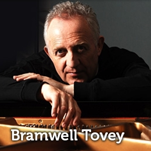 Photo of Bramwell Tovey, chin resting on his hands, resting on a piano