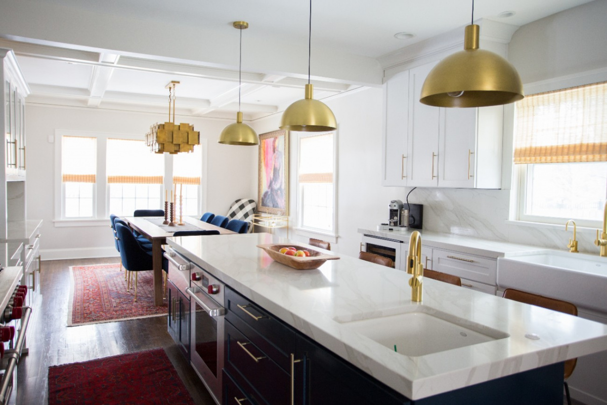 White countertop kitchen island with gold metal pendant lamps
