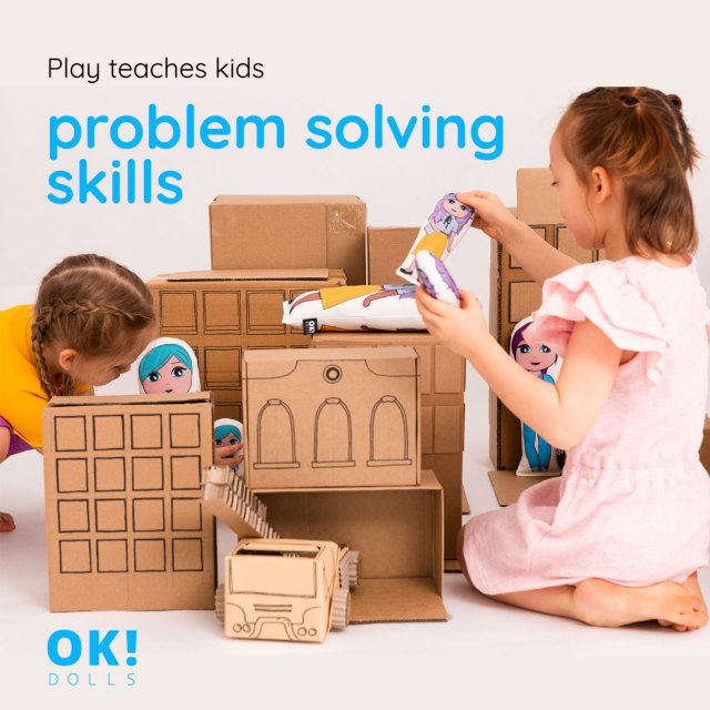 Girls playing with OK!Dolls and cardboard buildings