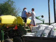 Katy and Kody fill the planter with corn seed.