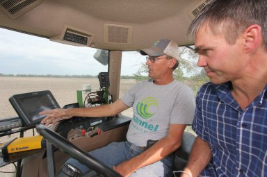Greg and Jens go over the auto steer and grain drill controls in the tractor cab.