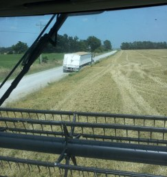 The combine approaching a semi on the side of the road, getting ready to unload another grain tank full of wheat.