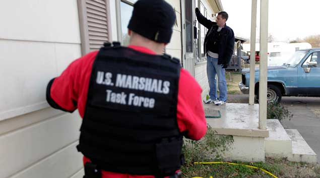 Tulsa Police Det. Andrew Mackenzie knocks on Kristy Rene Wade's door as Det. Eric Spradlin looks on as officers serve an arrest warrant Dec. 22, 2010. Wade was taken into custody.