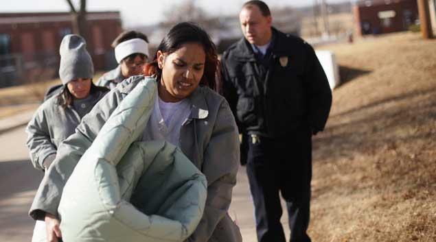 Patricia Spottedcrow carries her mattress and belongings to her dorm-style building inside Dr. Eddie Warrior Correctional Center on the first day of her incarceration at the facility. Spottedcrow received a 10-year prison sentence for selling a small amount of marijuana to a police informant with her children present in Kingfisher, Okla. Spottedcrow, a mother of four, had no prior criminal record.