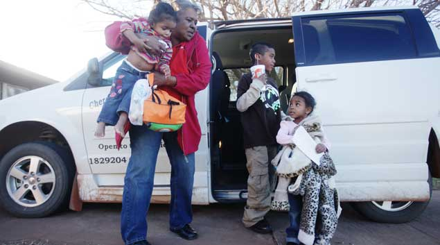 Grandmother Delita Starr holds Ja'zalynn Rex, 1, as Koby LeBlanc, center, 9, and Ja'alizah Rex, 3, exit a special transit van at the family's home in Kingfisher, Okla. The children's mother, Patricia Spottedcrow, received a 10-year prison sentence for selling a small amount of marijuana to a police informant with her children present. Starr cares for the children until Spottedcrow is released.