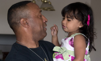 """Stephen Leon, a combat veteran who is now 70 percent disabled, holds his granddaughter Ashley A. De Leon at his apartment in Revere, Mass. in June. Leon said that before he found an independent advocate he didn't think anyone at the VA would give him a """"dime"""" for claims."""