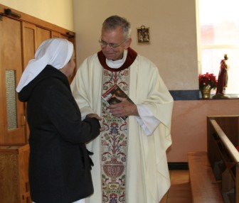 Father Michael Chapman greets a member of his congregation for morning Mass at Holy Angels Church in Oklahoma City.