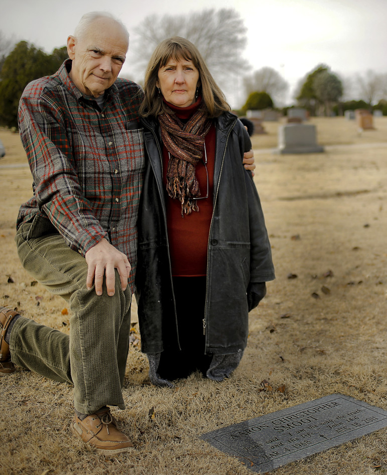 Dwight and Jill Smooth, next to the headstone of their son Aaron Smoot.