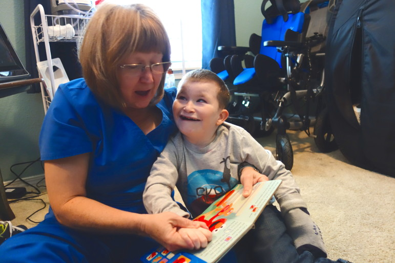 Home health nurse Rita Nuss reads a book to 9-year-old Josiah Melton, who has a number of chromosomal disorders and is on the Developmental Disability Services waiver waiting list.