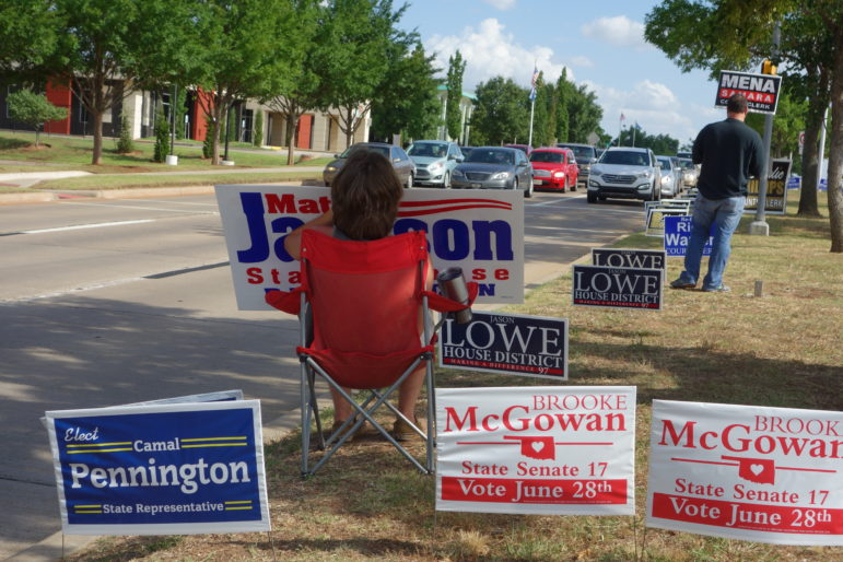 Campaign supporters held signs and waved to motorists Thursday as they passed the Oklahoma County Board of Elections.
