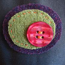 Brosch i lila och grönt, gjord av ylletröjor och en knapp