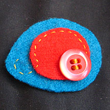 Brosch i turkos och rött, gjord av ylletröjor och en knapp