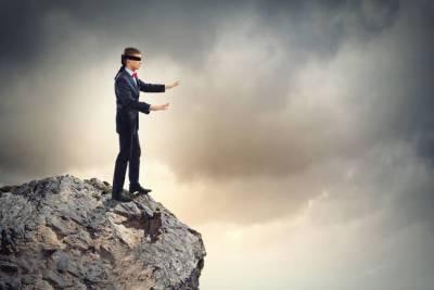 blindfolded man in danger of walking off cliff