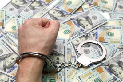 Hand in handcuffs on a pile of dollars