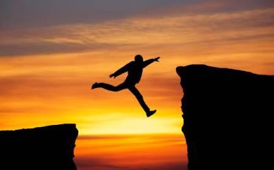 man jumping across gap