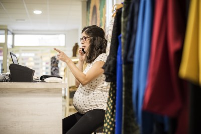 Pregnant woman working in clothes store