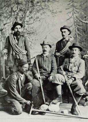 Phillimore e Raynor con le guide Giuseppe Colli, Antonio Dimai, Arcangelo Dibona. Lo sfondo è dipinto