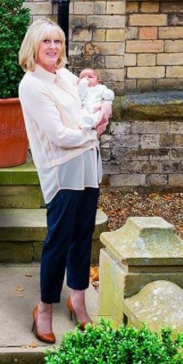Sarah Lancashire holds a small child.