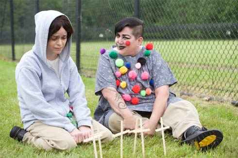 Taryn Manning and Lea DeLaria sit on the grass. Lea is covered with colored balls
