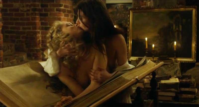 Malin Buska and Sarah Gadon kiss on a large Bible
