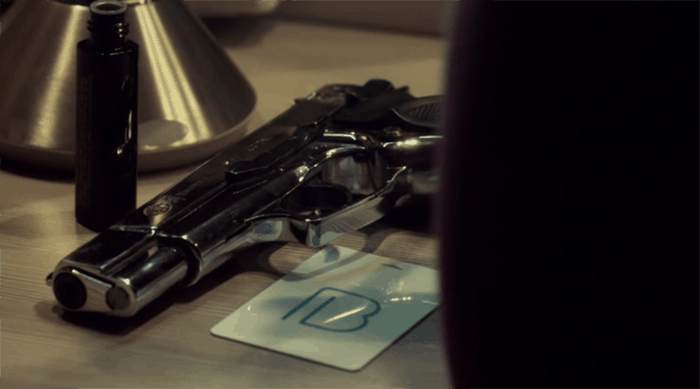 Beth's gun and a card with a symbol on it.