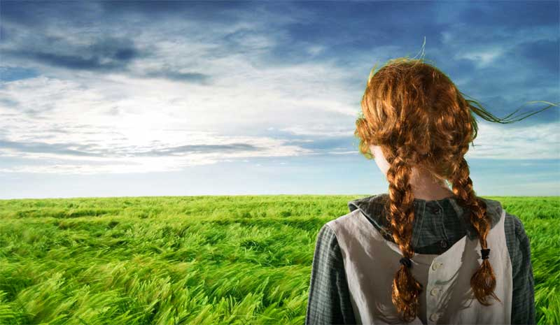 a landscape scene from Anne with an E. Amybeth McNulty has her back to the camera