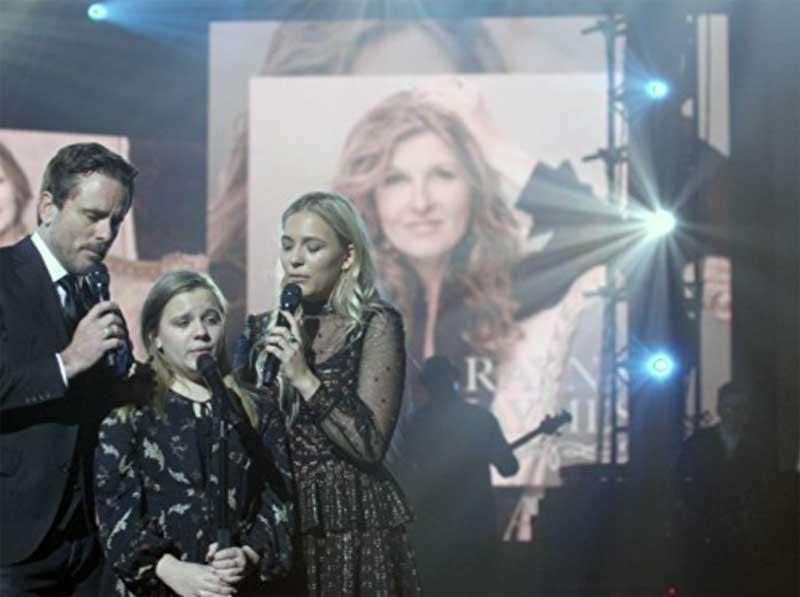 Charles Esten, Maisy Stella and Lennon Stella in front of a poster sized image of Connie Britton in Nashville
