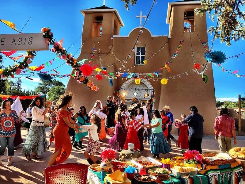 A fiesta in front of an adobe church