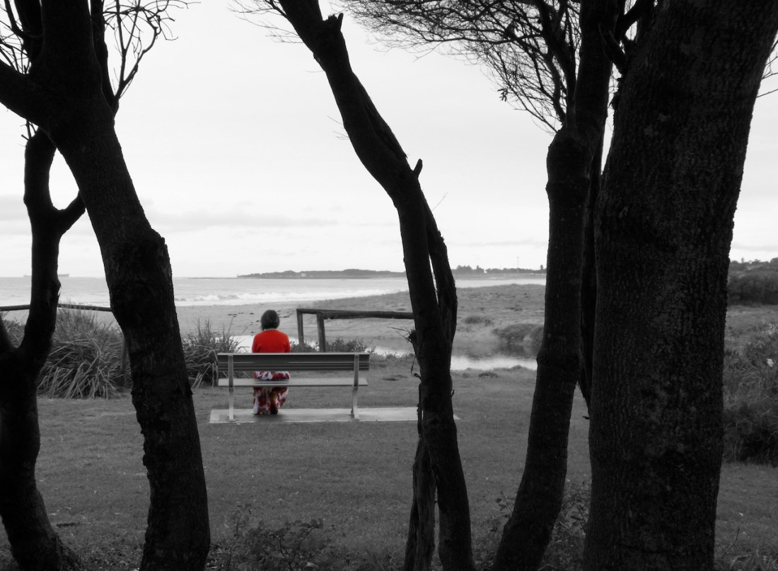 A woman sitting on a park bench. The photo is blacka nd white excpet for the woman's red jumper and dress. It is a dark and desolate scene with the sea in the backgrond.