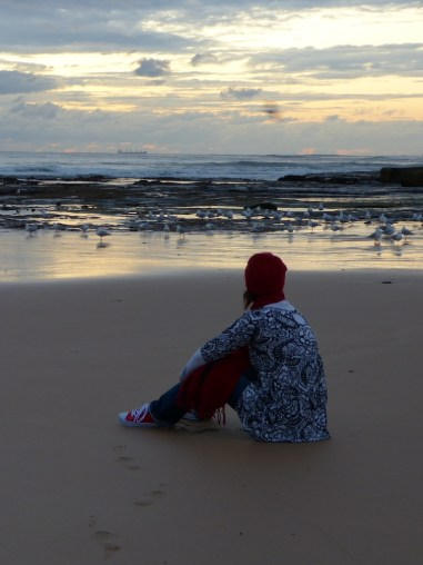 A woman in a black and white top sitting on the sand facing away fromt he camera. It is very early morning and the sun has not yet risen. The waves are in the background.
