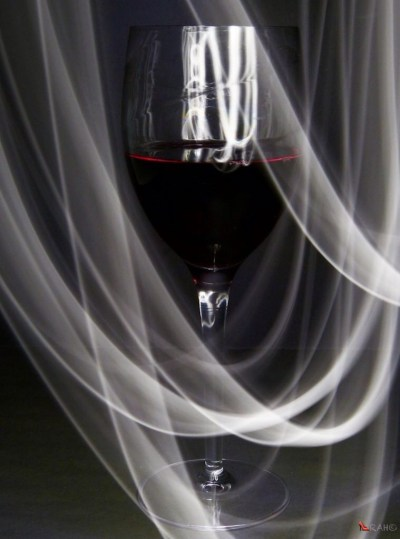 A glass of red wine with a veil of white light made with a torch and slow shutter speed