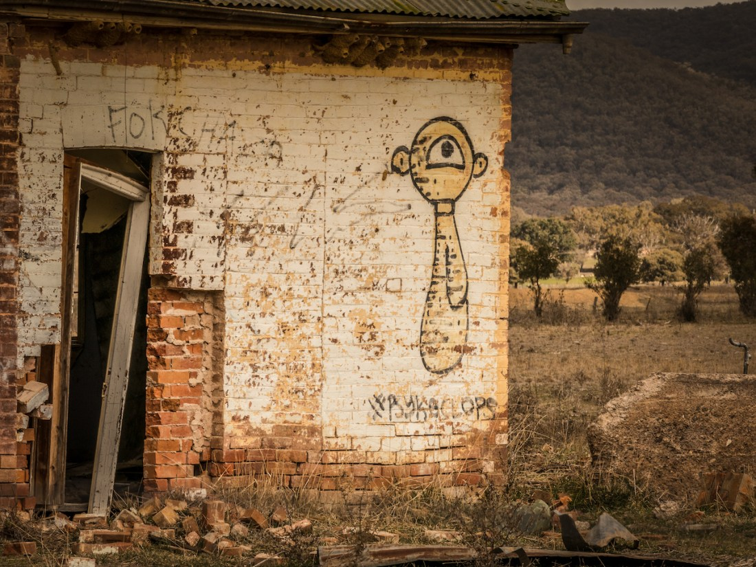 A cartoon person with one eye is painted on an old abandoned building.