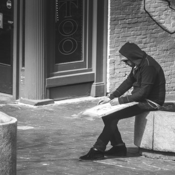 a man in a hooded jacket drawing on a large piece of board on the street
