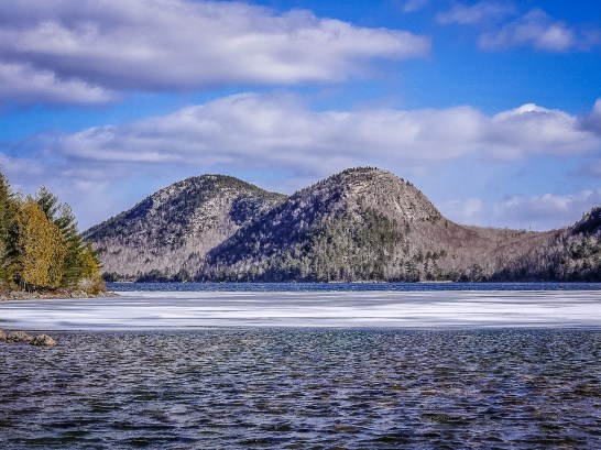 two domes shaped mountaind stand behind a lake with floating ice