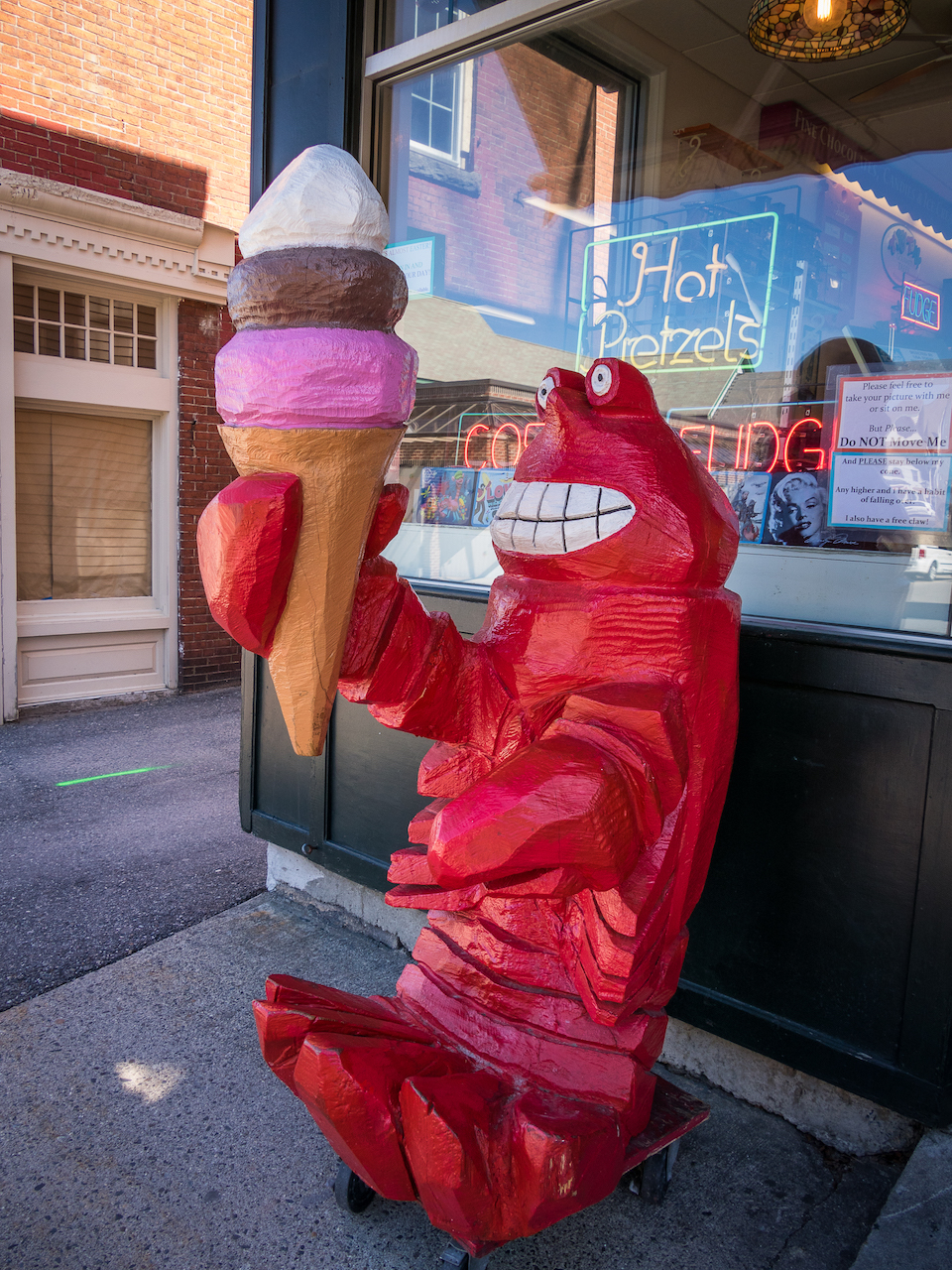A large red carved wooden model of a lobster holds an ice cream