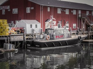 A pilot boat docked at a wharf