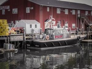 A pilot boat docked at a wharf