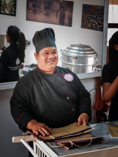a chef dressed in black smiles as he holds a cook book.