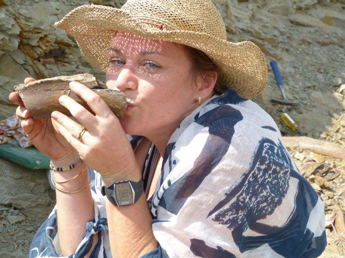 a women in a straw hat is kissing a dinosaur bone