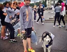 Бегун стоит с собакой