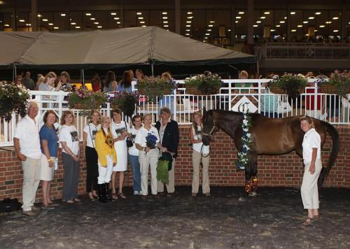 """Thoroughbred Retirement Foundation (TRF) at James River celebrating Multiple Choice in the Winner's Circle as """"Mr. TRF."""" Pictured from left to right: Dr. Tom Newton; Robin Richards, Virginia breeder and national president of the Horsemen's Benevolent and Protective Association; Nancy Philpy; Deirdre Feeney; Chelsey Keiser, jockey who placed the wreath in honor of all racehorses; Robin Williams, former national president of TRF and founder of James River Chapter; Jennifer Ernst; Anne Tucker, president of James River chapter; Jeanna Bouzek, representing Colonial Downs; Ari Brothers; and Stephanie Nixon. Photo courtesy of Coady Photography"""