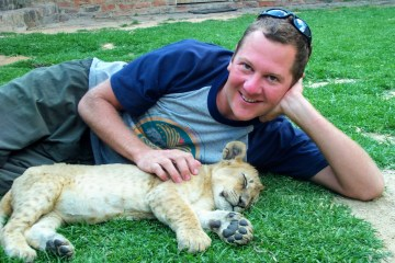 Henry Malmgren with a sleeping lion cub.