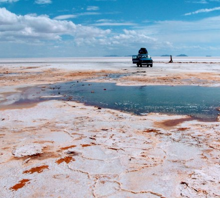 The water holes are the only relief on the white salt flats.